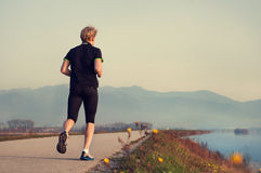 Young man jogging near the lake. On the background of beatiful mountain view Stock Image
