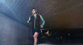 Young man jogging at night in city. Fit male athlete running under a bridge Royalty Free Stock Images