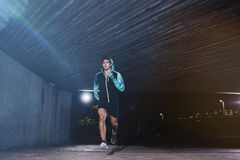Young man jogging at night. Full length shot of a young man jogging at night. Fit male athlete running under a bridge Royalty Free Stock Photography