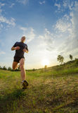 Young man jogging outdoors. Legs of a man with a low angle. Against the background of the blue sky with patches of sunlight Royalty Free Stock Image