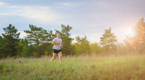 Young man jogging outdoors. The man is running up the hill. Solar flare from sunset Stock Photo
