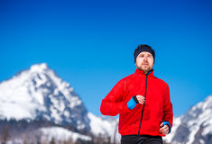 Young man jogging. Outside in sunny winter mountains Stock Image