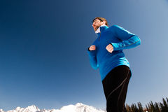 Young man jogging. Outside in sunny winter mountains Royalty Free Stock Photos