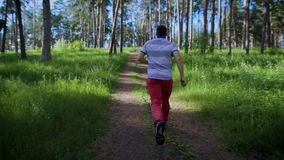 Young man jogging in the park. He accelerating and running on the limits. Back view stock footage