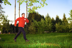 Young man jogging in the park. The image of young man jogging on a footpath in the city park on the background of bright green leaves, just bloomed in the spring Stock Photo