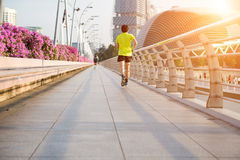 Young man is jogging on road. Royalty Free Stock Photography