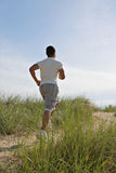 Young Man Jogging in the Sandy Beach Area Stock Photos