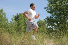 Young Man Jogging in the Sandy Beach Area Stock Image