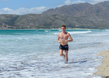 Young man jogging on the sea beach Royalty Free Stock Photo