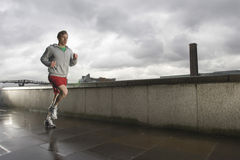 Young Man Jogging On Stormy Day. Young man jogging besides the Thames river in London on a stormy day Royalty Free Stock Photography
