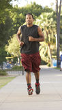 Young Man Jogging On Street. Coming Towards Camera Royalty Free Stock Photography