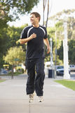Young Man Jogging On Street. Looking Off Camera Stock Photo