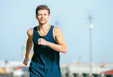 Young man jogging at the street in summer morning time Stock Photo