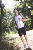 Young Man Jogging Through Woodland Royalty Free Stock Images
