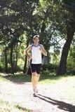 Young Man Jogging Through Woodland Royalty Free Stock Photos