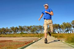 Young man jogs on woodwalk Royalty Free Stock Photography