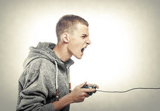 Young man with a joystick. For game console side view. Toned photo stock photography