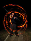 Young man juggling fire poi. Fire poi juggled by a young man, paint with fire Royalty Free Stock Photos