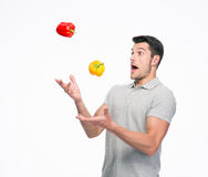 Young man juggling pepper Royalty Free Stock Photography