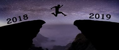 A young man jump between 2018 and 2019 years over night sky with stars and through on the gap of hill silhouette evening colorful royalty free stock images