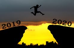 A young man jump between 2019 and 2020 years over the sun and through on the gap of hill silhouette evening colorful sky. royalty free stock photos