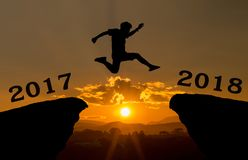 A young man jump between 2017 and 2018 years over the sun and through on the gap of hill silhouette evening colorful sky. stock image