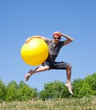Young man jump with yellow ball Stock Photos