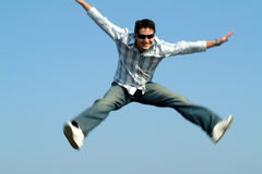 Young man jumping. Against blue sky Royalty Free Stock Photography