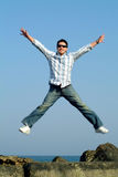 Young man jumping. Against blue sky Royalty Free Stock Photos