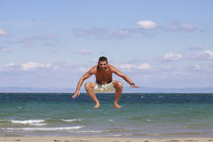 Young man jumping against blue sky and sea. Athletic young man enjoying the summer, jumping in a Bulgarian,Black sea beach Stock Photos