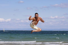 Young man jumping against blue sky and sea. Athletic young man enjoying the summer, jumping in a Bulgarian,Black sea beach Royalty Free Stock Images