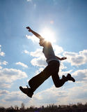 Young man jumping against cloudy sky Stock Photography