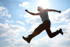Young man jumping against cloudy sky Stock Photo