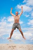 Young man jumping in the air against a blue sky. Young man jumping and raising hands in the air against a blue sky Stock Photo