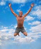 Young man jumping in the air against a blue sky. Young man jumping and raising hands in the air against a blue sky Royalty Free Stock Image
