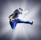 Young man jumping in air against light background Stock Photos