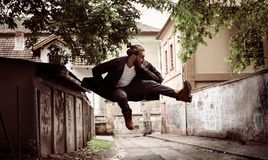 Businessman jumping on street alone. Royalty Free Stock Photos