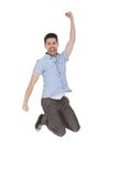 Young man jumping with arms raised Stock Image
