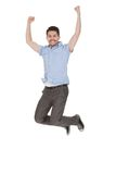 Young Man Jumping With Arms Raised Stock Photo