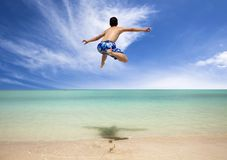 Young man jumping on the beach Stock Photos
