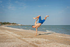 Young man jumping on beach. Young man jumping, fun sports on beach Royalty Free Stock Photo