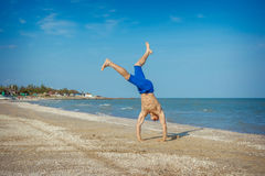 Young man jumping on beach. Young man jumping, fun sports on beach Stock Image