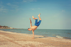 Young man jumping on beach. Young man jumping, fun sports on beach Royalty Free Stock Photography
