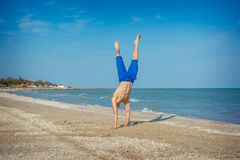 Young man jumping on beach. Young man jumping, fun sports on beach Royalty Free Stock Images