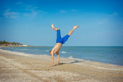 Young man jumping on beach. Young man jumping, fun sports on beach Stock Photo