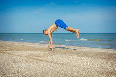 Young man jumping on beach. Young man jumping, fun sports on beach Royalty Free Stock Image