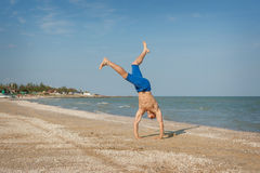 Young man jumping on beach. Young man jumping, fun sports on beach Stock Images