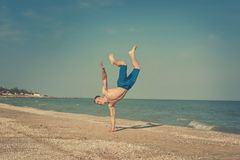 Young man jumping on beach. Young man jumping, fun sports on beach. Retro toned Stock Images