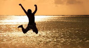 Young man jumping on the beach at sunset stock images