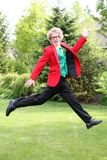 Young man jumping with brightly colored suit Royalty Free Stock Photos